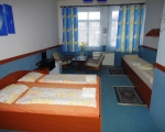 Čtyřlůžkový pokoj s jednou manželskou postelí a posezením